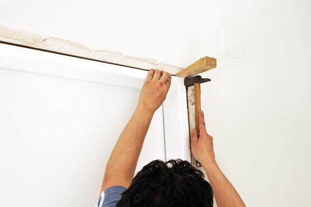 Verzogene Tür mit Holzkeilen in Form bringen