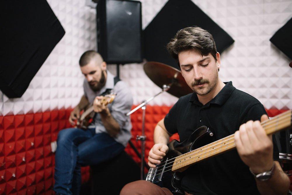 Männer spielen im Musikzimmer Gitarre