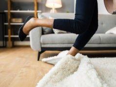 Frau stolpert über Teppichkante