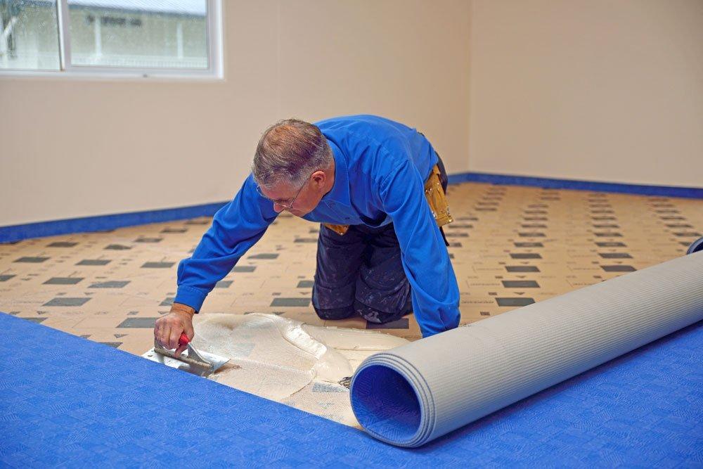 Mann klebt Teppich am Boden fest