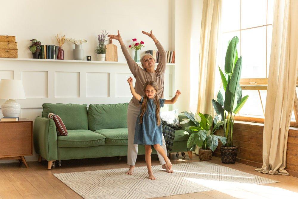 Oma und Enkelin tanzen im Wohnzimmer